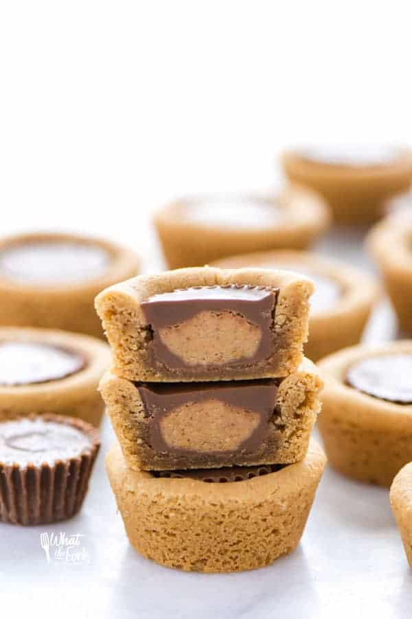 Gluten Free Reese's Peanut Butter Cookie Cups are a chocolate + peanut butter lovers' dream cookie! They're peanut butter cookies baked in mini muffin tins then stuffed with peanut butter cups. Simply amazing! SUPER EASY cookie recipe to make too! Recipe from @whattheforkblog | whattheforkfoodblog.com | gluten free cookie recipes | easy dessert recipes | homemade peanut butter cookies | how to make peanut butter cookies | #glutenfree #chocolate #peanutbutter #cookies #dessert #easyrecipes