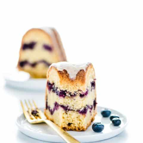 Piece of Gluten Free Blueberry Coffee Cake on a white plate garnished with blueberries and a gold fork.