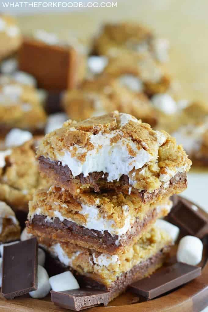 Gluten Free S'mores Bars stacked on a brown wood platter with a bite taken out from What The Fork Food Blog
