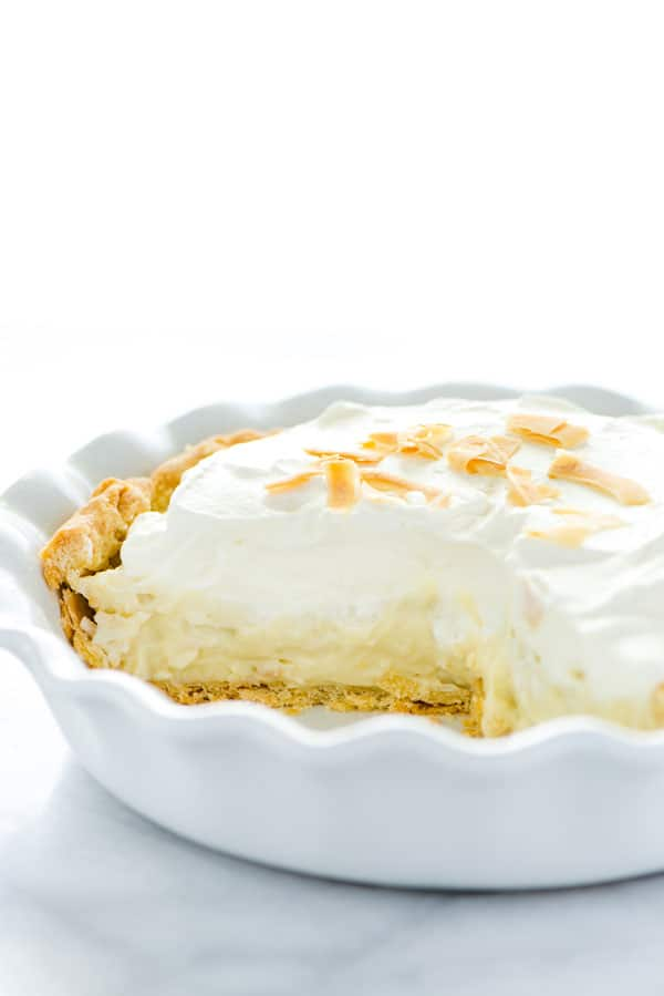 Gluten Free Coconut Cream Pie in a white pie dish with a slice cut out