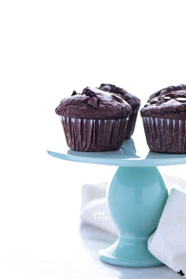 gluten free Bakery Style Double Chocolate Chip Muffins displayed on a blue cake stand