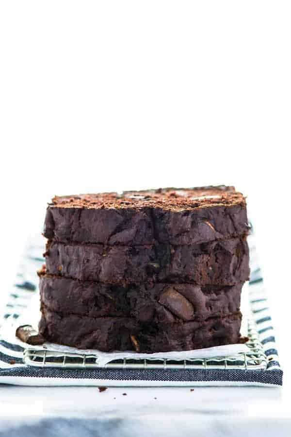 Gluten Free Double Chocolate Zucchini Bread sliced and stacked on a striped towel and rack