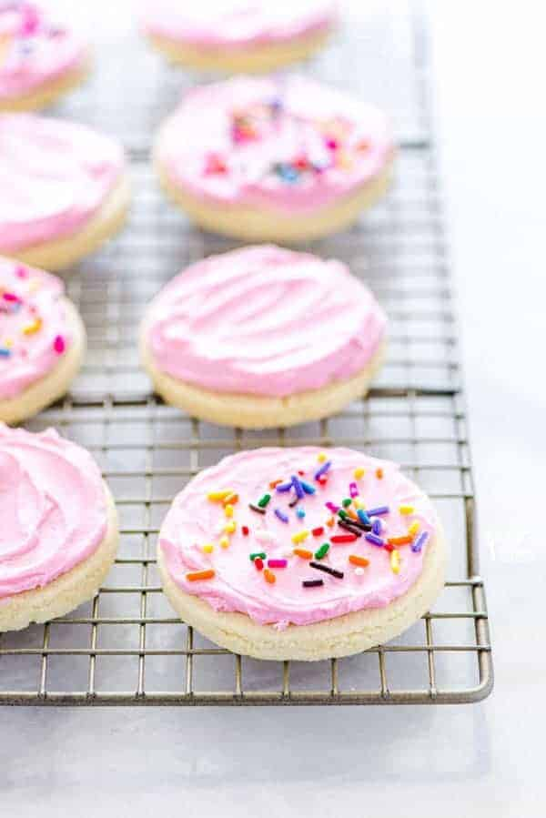 Gluten Free Frosted Sugar Cookies on a wire rack decorated with pink frosting and rainbow sprinkles