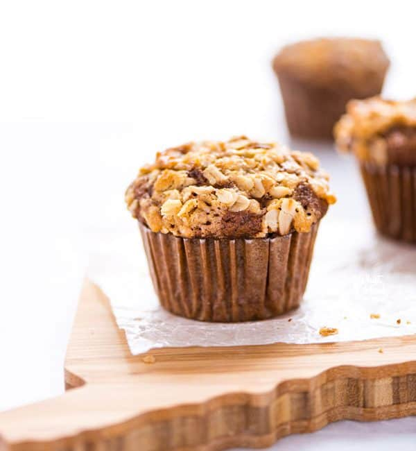 A gluten free banana oat muffin on wax paper on top of a wood cutting board
