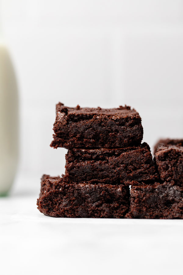 sliced gluten free brownies on a parchment paper lined wood cutting board