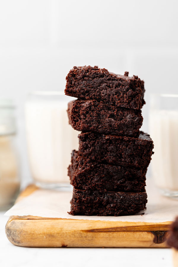 fudgy gluten free brownies stacke don a wood cutting board lined with white parchment paper