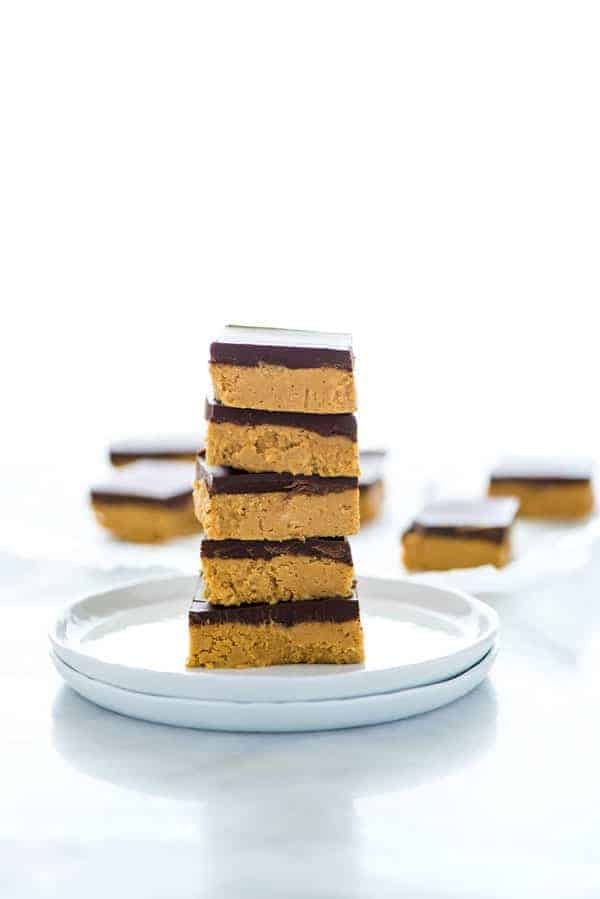 A stack of gluten free chocolate peanut butter bars on a white plate.