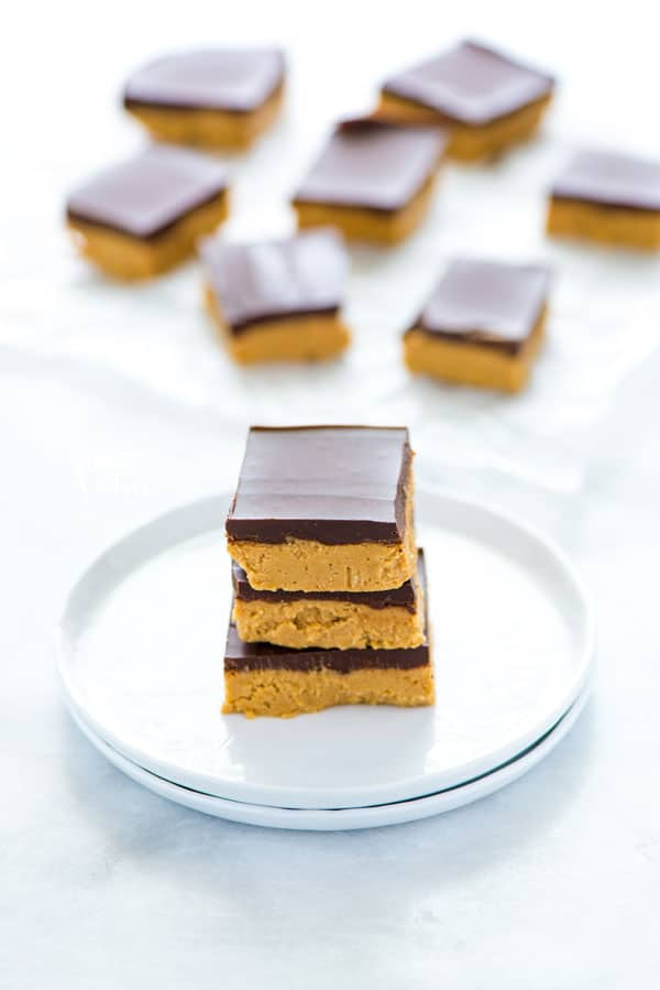 3 gluten free chocolate peanut butter bars stacked on a white plate.