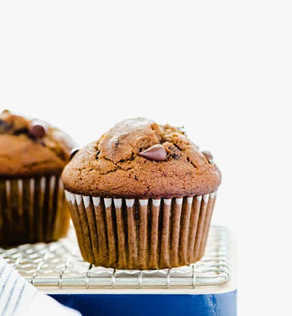 Gluten Free Pumpkin Chocolate Chip Muffins cooling on a wire rack and cutting board