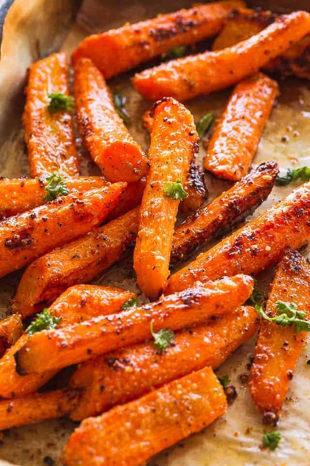 roasted carrots on a sheet pan garnished with chopped fresh parsley