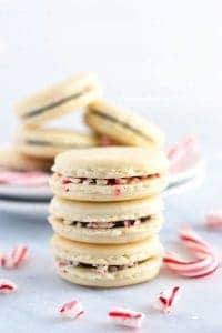 Gorgeous Macarons flavored for Christmas! These peppermint macarons are made with a basic macaron shell and filled with peppermint chocolate ganache and crushed candy canes - they're heavenly! Gluten free and dairy free macaron recipe from @whattheforkblog | whattheforkfoodblog.com | Sponsored | how to make macarons | easy macaron recipe | french macarons | macaroon | french macaron filling | french macaron flavors | macaron recipe flavors
