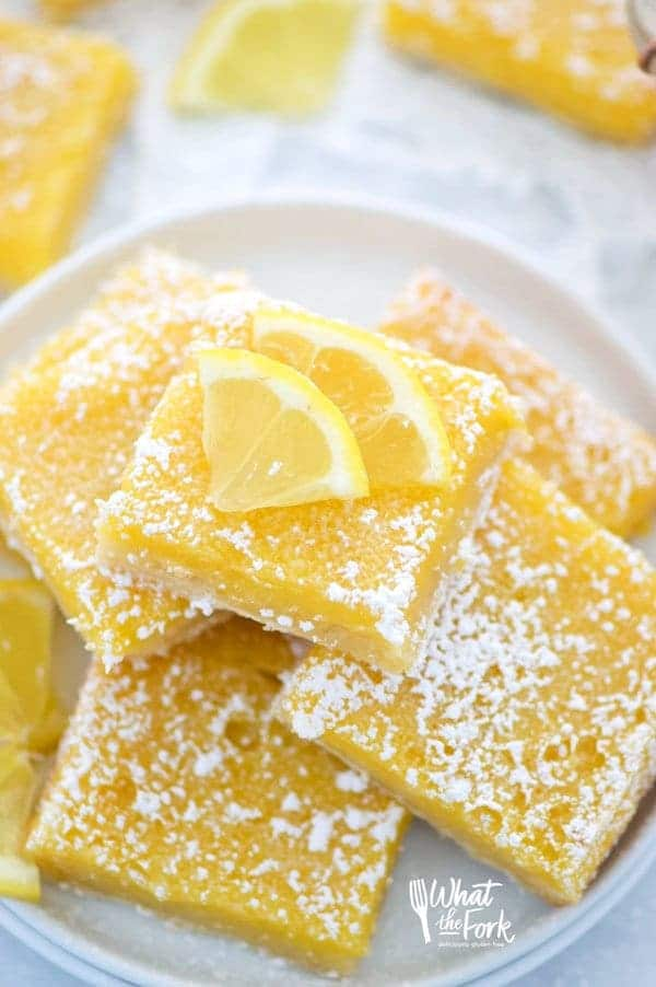 Easy and delicious gluten free lemon squares. They're not too tangy and just sweet enough! Perfect for Easter, bridal showers, baby showers, or any dessert table. Recipe from @whattheforkblog | whattheforkfoodblog.com | Sponsored | lemon bars | gluten free desserts | easy gluten free recipes | Spring desserts | lemon custard with shortbread crust | best recipes | gluten free baking