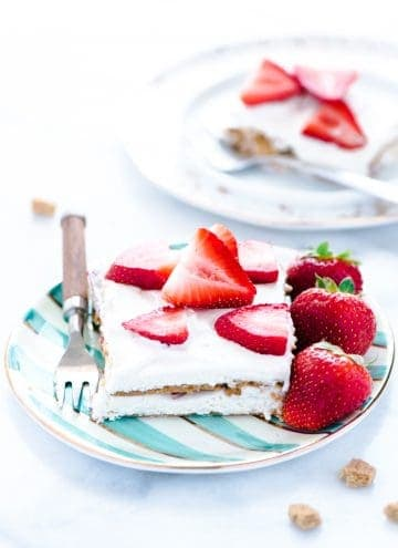 A piece of Gluten Free Strawberry Icebox Cake on a green and white striped plate with a fork. Plate is garnished with whole strawberries.