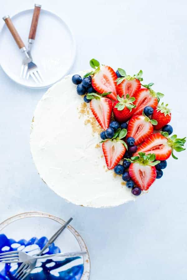 A whole, easy no bake cheesecake topped with fresh strawberries and blueberries