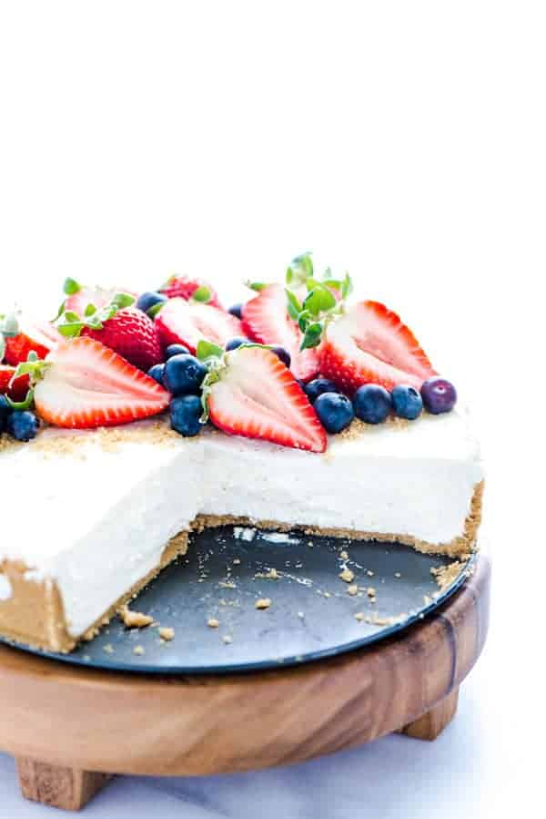 View of sliced no bake cheesecake with fresh berries on a wooden cake stand