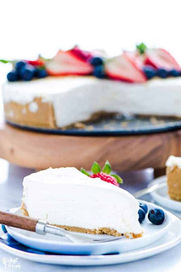 Slice of no bake cheesecake on a plate with a fresh strawberry and blueberries.