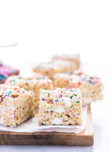 Gluten Free Rice Krispies Treats arranged on a brown wood cutting board