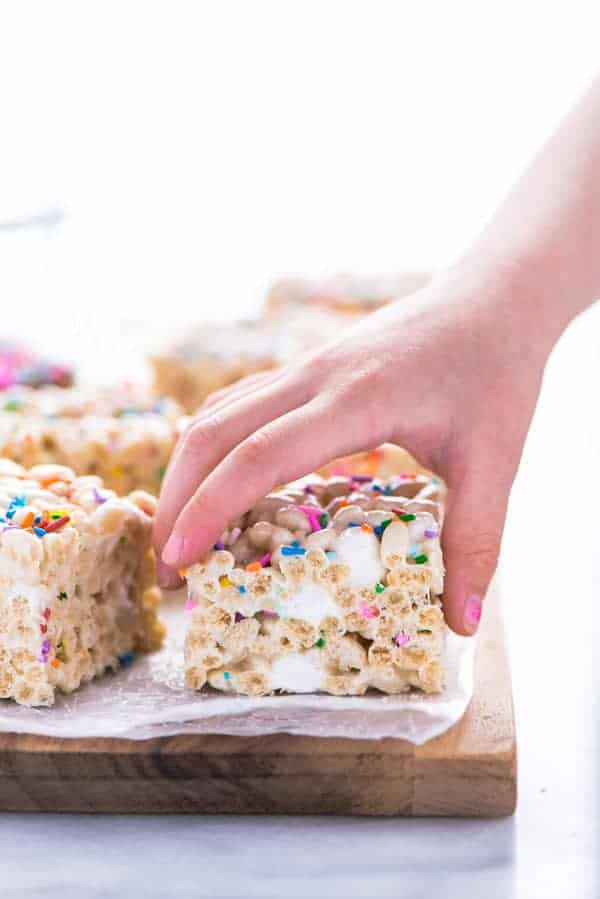 A hand taking a gluten free rice krispies treat off of a brown wood cutting board