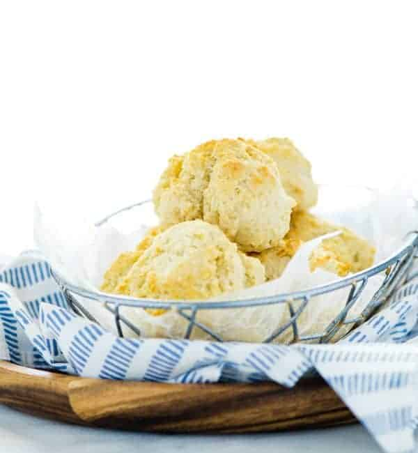 Gluten Free Drop Biscuits in a wire bread basket with a blue towel