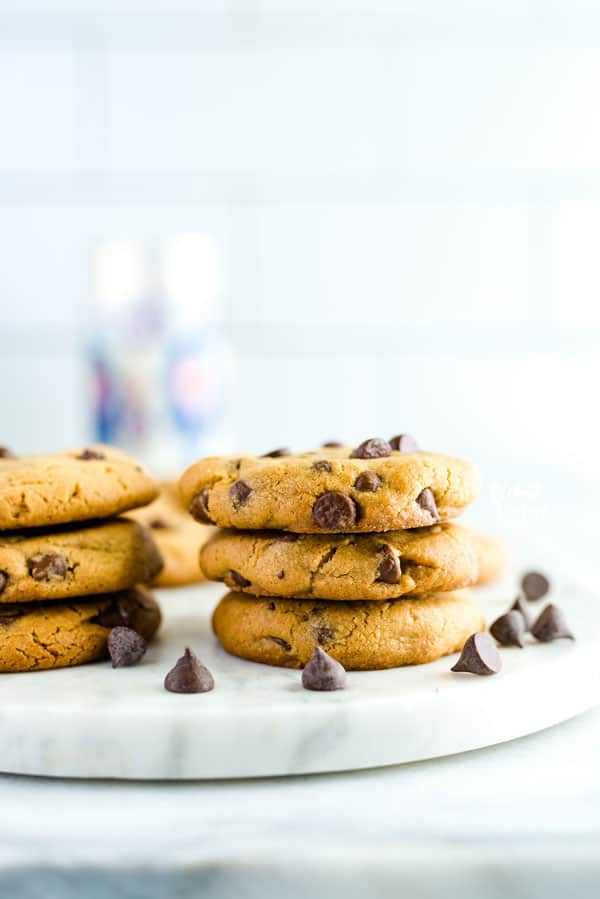 Stack of gluten free peanut butter chocolate chip cookies on a marble slab garnished with chocolate chips