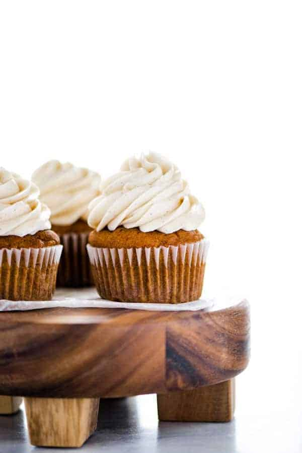 Gluten Free Pumpkin Cupcakes with Cinnamon Cream Cheese Frosting on a round wood cake stand