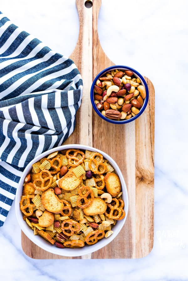 Gluten Free Chex Mix in a white bowl on a wood cutting board with a bowl of mixed nuts and a striped towel.