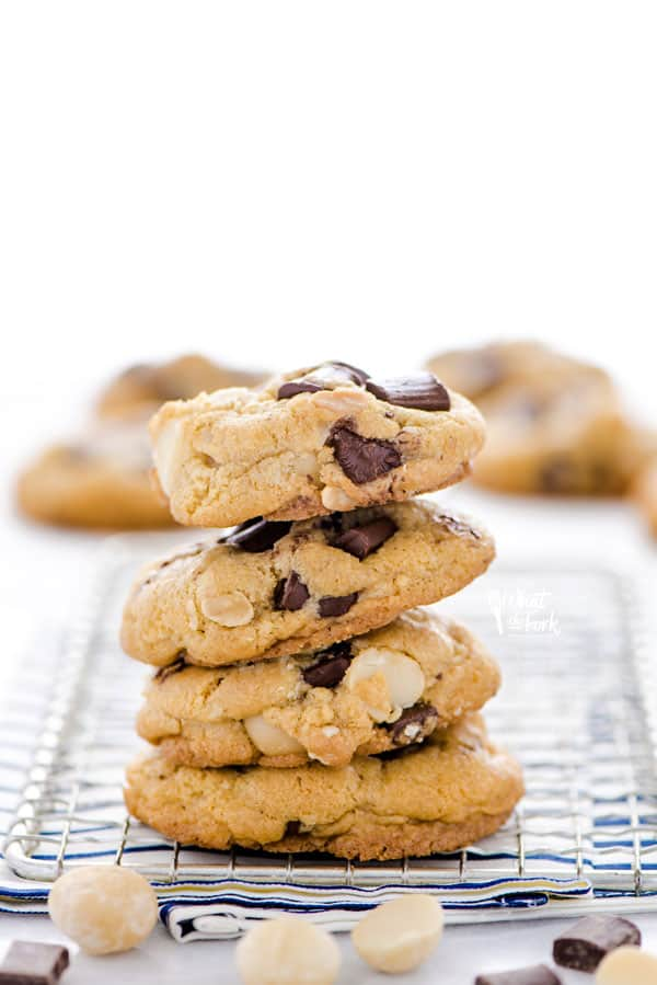 A stack of gluten free Chocolate Macadamia Nut Cookies on a small wire rack.
