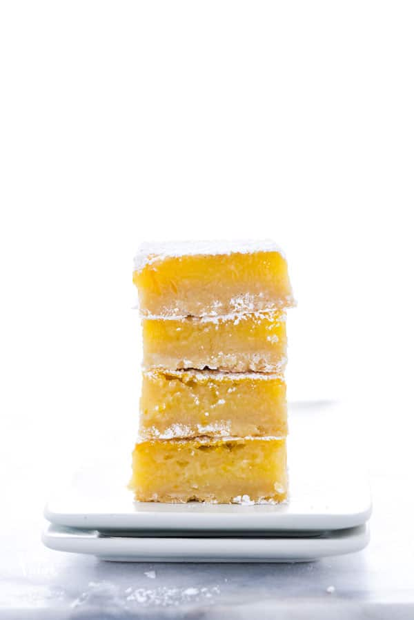 A stack of four gluten free Meyer Lemon Bars on a square white plate