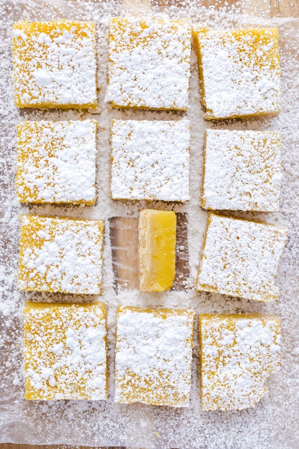 Sliced gluten free Meyer Lemon Bars on a cutting board dusted with powdered sugar