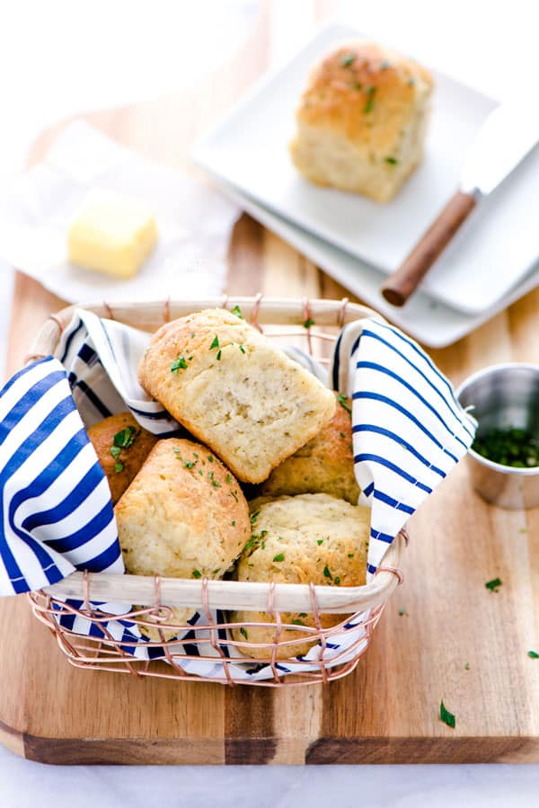 Gluten Free Rolls in a wire basket with a blue and white striped napkin placed on a wood cutting board