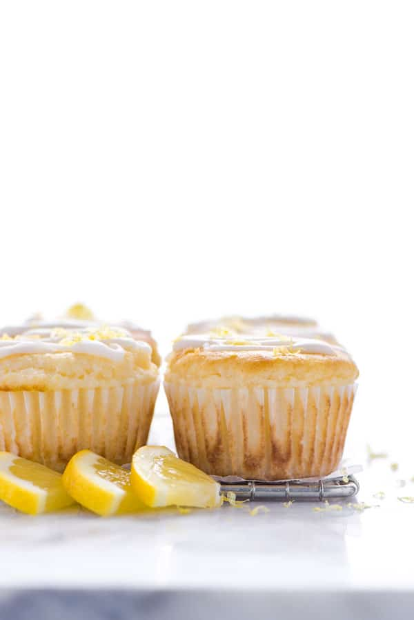 Gluten Free Lemon Ricotta Muffins on a wire rack garnished with lemon slices
