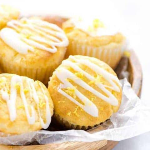 Closeup of Gluten Free Lemon Ricotta Muffins in a wood bowl lined with wax paper