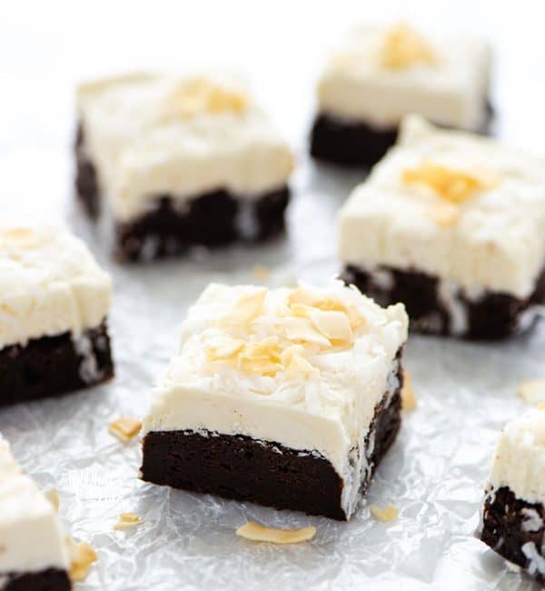 Slices of Gluten Free Brownies with Coconut frosting on wax paper ready to serve.
