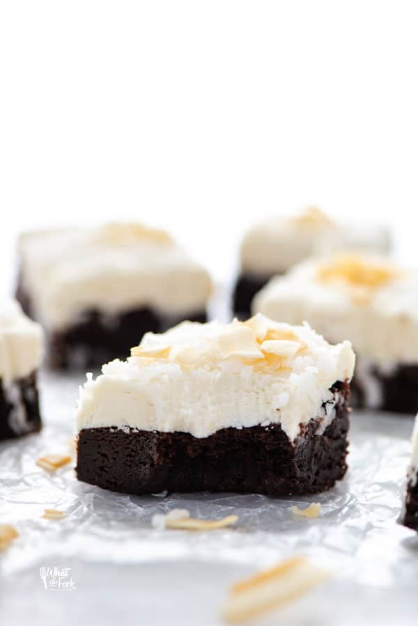 Rich and fudgy gluten free brownies are topped with creamy coconut frosting for the ultimate decadent dessert! These brownies are so full of chocolate and coconut flavor and they just melt in your mouth. Bring them to your next party or potluck! Top them with toasted coconut or toasted coconut chips for the best coconut dessert to make for a crowd. Gluten free brownie recipe from @whattheforkblog - visit whattheforkfoodblog.com for more gluten free dessert recipes! #glutenfree #brownies #coconut