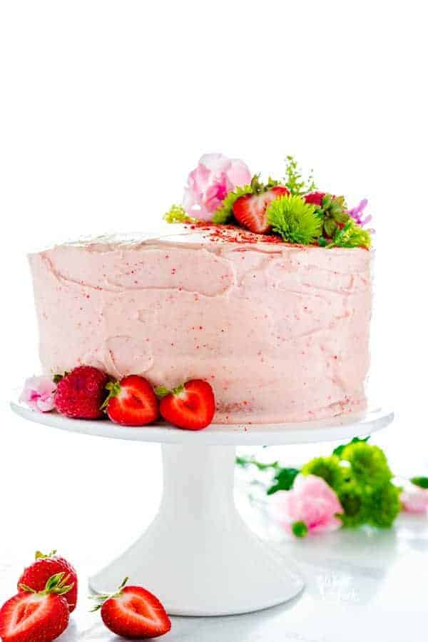 Homemade Gluten Free Strawberry Cake on a white cake stand garnished with fresh strawberries and flowers