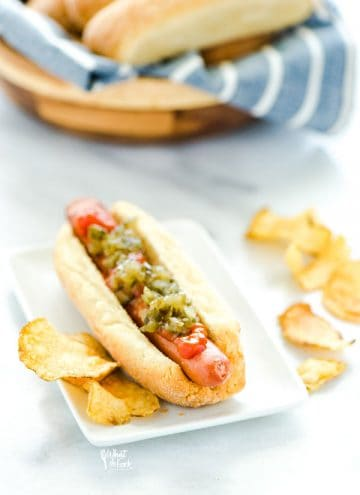 Gluten Free Hot Dog Buns filled with a hot dog and topped with ketchup and relish and potato chips on the side.
