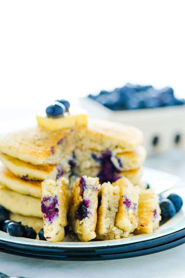 Easy homemade fluffy Gluten Free Blueberry Pancakes are full of fresh blueberries bursting with flavor. Great for breakfast, brunch, or dinner. Plus they freeze well so make a double batch to save some for later! This recipe makes the best blueberry pancakes! Gluten Free breakfast recipe from @whattheforkblog - visit whattheforkfoodblog.com for easy gluten free recipes! #glutenfree #pancakes #breakfast #easyrecipe #blueberry #blueberrypancakes