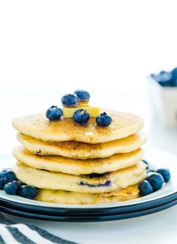 Gluten Free Blueberry Pancakes stacked on a plate and garnished with fresh blueberries