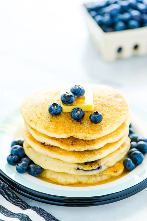 gluten free blueberry pancakes stacked on a plate and garnished with a pat of butter and fresh blueberries