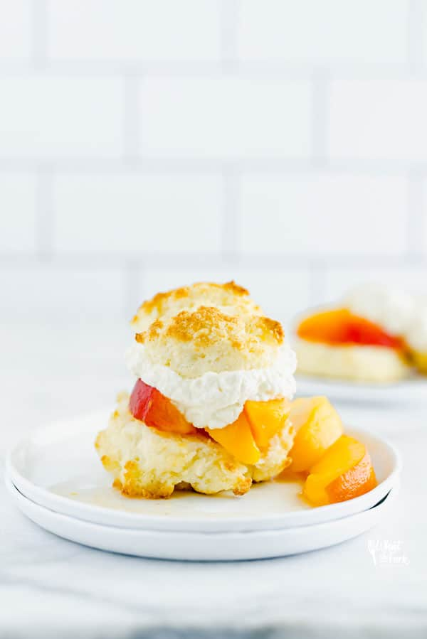 Gluten Free Peach Shortcake on a white plate garnished with fresh peaches