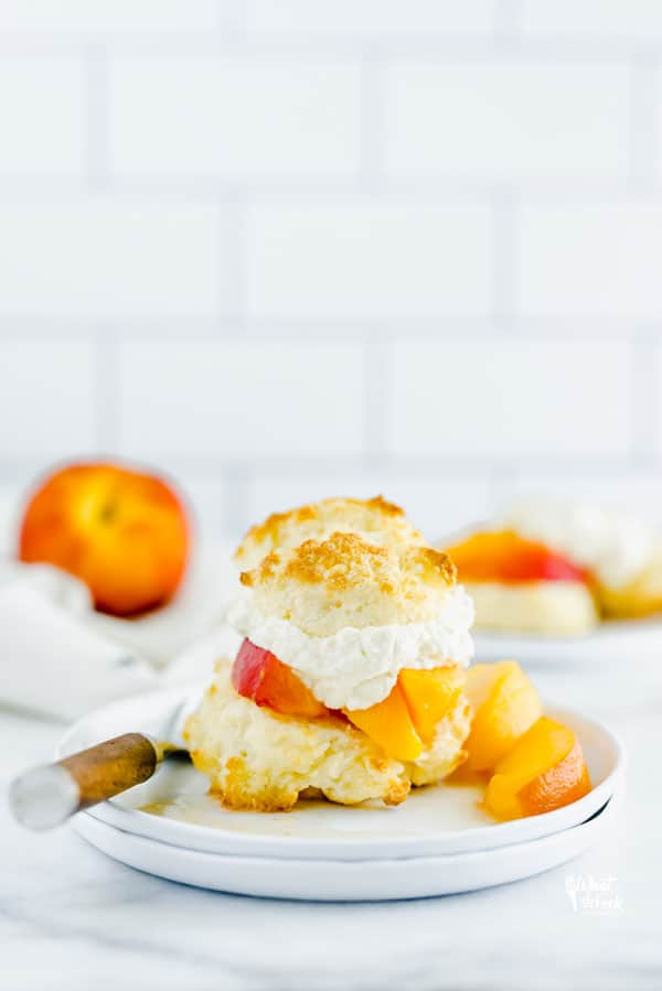 Easy gluten free peach shortcake is made with gluten free drop biscuits that are topped with fresh sweetened peaches and homemade whipped cream. It's the perfect summer dessert to share during peach season. This recipe is best with fresh peaches! Easy gluten free dessert recipe from @whattheforkblog - visit whattheforkfoodblog.com for more gluten free dessert recipes! #glutenfree #peach #peachshortcake #dessert #glutenfreedessert #easyrecipe #shortcake