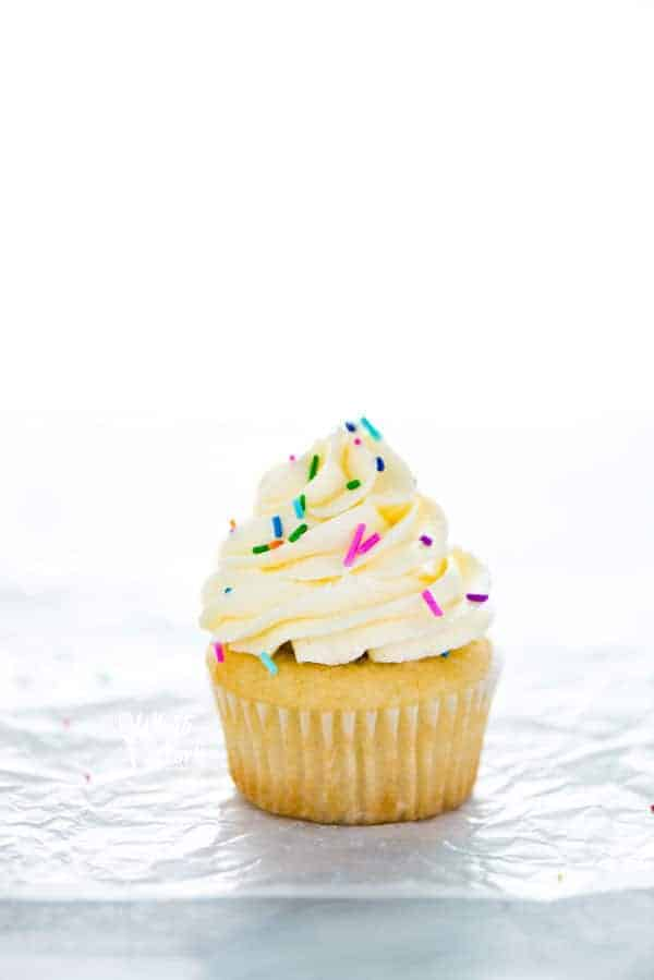Gluten Free Vanilla Cupcakes with a single cupcake with vanilla frosting and sprinkles