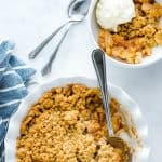 Gluten Free Apple Crisp features warm, spiced apples and a crisp oatmeal cookie-like topping. It's the perfect dessert to make in the fall! Follow this recipe and you'll make the best apple crisp recipe every time that's full of flavor and contrasting textures. It's an old fashioned recipe with a modern twist. Serve it with vanilla ice cream or homemade whipped cream! Visit whattheforkfoodblog.com for more gluten free desserts. #applecrisp #bestapplecrisp #glutenfree #fallbaking #applerecipes