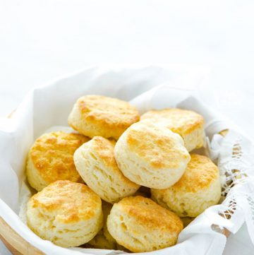 Gluten Free Buttermilk Biscuits in a wood bowl lined with a white towel