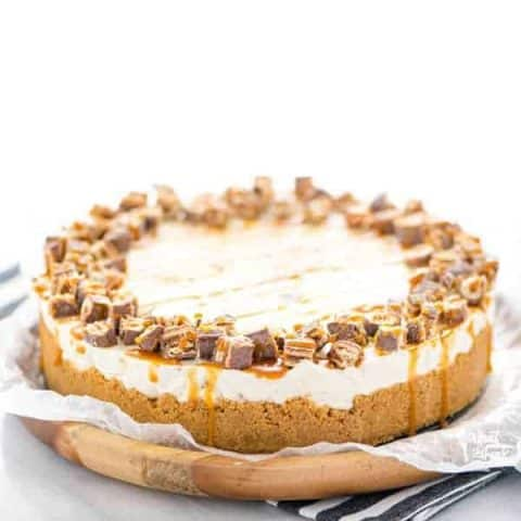 Gluten Free Chocolix No Bake Cheesecake recipe on a round wood board lined with wax paper.