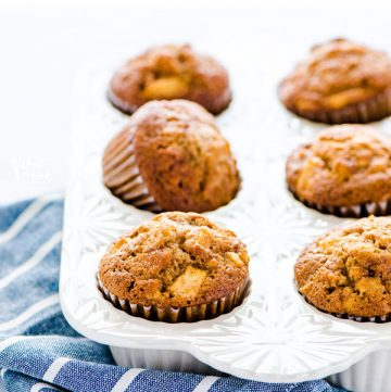 Gluten Free Apple Muffins in a white muffin pan on a blue and white striped kitchen towel.