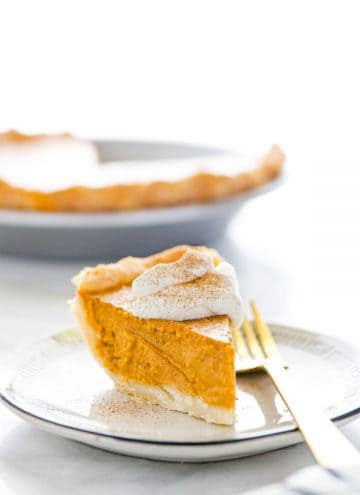 A piece of gluten free pumpkin pie on a white plate topped with whipped cream and dusted with cinnamon sugar