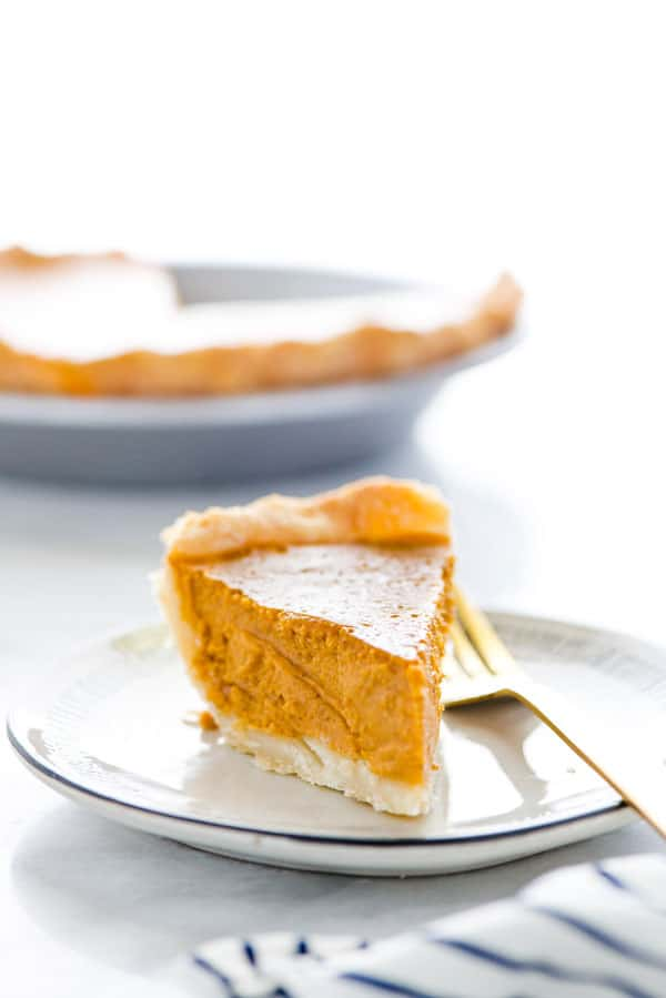 This is a classic, easy recipe for Gluten Free Pumpkin Pie. It's made with a flaky pie crust, creamy pumpkin filling, and warm spices. This is THE pumpkin pie for your Gluten Free Thanksgiving! There's a dairy free and lactose free option in the recipe notes with a Gluten Free Pie Crust recipe too. Gluten Free Pie Recipe from @whattheforkblog - visit whattheforkfoodblog.com for more gluten free desserts. #glutenfree #pumpkinpie #Thanksgiving #glutenfreedesserts #glutenfreepie