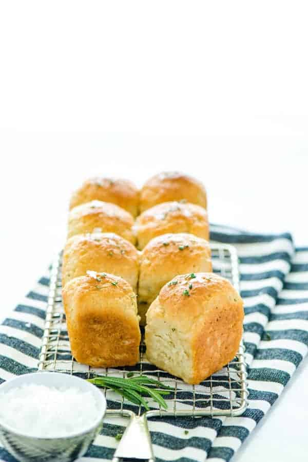 Gluten Free Rosemary Rolls on a wire rack and striped towel