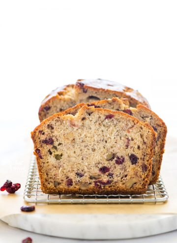 Sliced Gluten Free Cranberry Bread on a wire rack and marble board